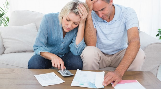 Worried couple going over finances at home in living room